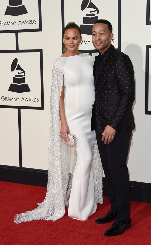 Singer-songwriter John Legend and his wife Chrissy Teigen arrive on the red carpet during the 58th Annual Grammy Music Awards in Los Angeles February 15, 2016. AFP PHOTO/ Valerie MACON / AFP / VALERIE MACON        (Photo credit should read VALERIE MACON/AFP/Getty Images)