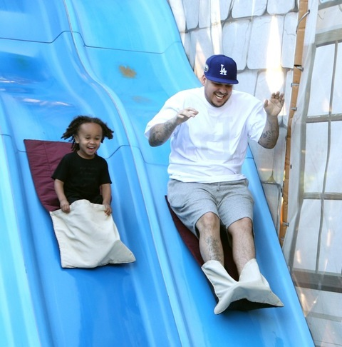 **PREMIUM RATES APPLY**  Rob Kardashian enjoys a day at Legoland with girlfriend Blac Chyna and rides a slide with her son King Cairo in Los Angeles. Rob was holding a water bottle as he walked with his girl and her son through the fun park. Rob was also spotted taking photos of her as the group went through their fun day together. They were also laughing together as they rode on the back of a rollercoaster with other members of her family a day before his birthday.